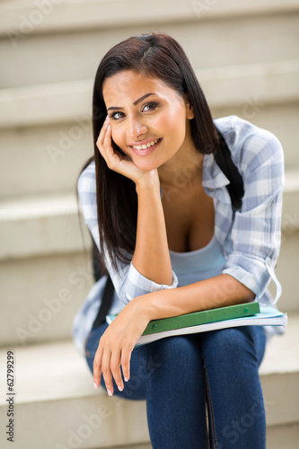 young female college student sitting outdoors