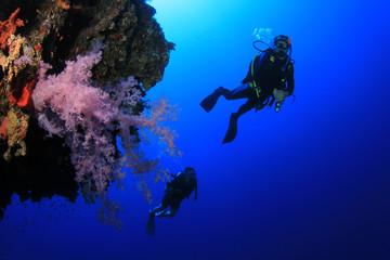 Scuba divers explore coral reef wall