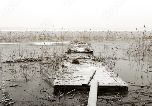 Broken wooden jetty in frozen lake