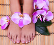 Pedicure with pink orchid flowers on bamboo mat