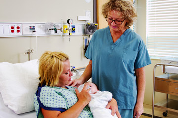 Nurse observing Mom feeding baby