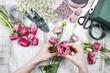 Leinwanddruck Bild - Florist at work. Woman making beautiful bouquet of pink eustoma
