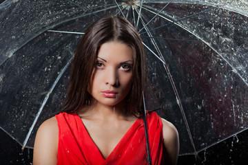 Young pretty woman with umbrella under rain on a dark background