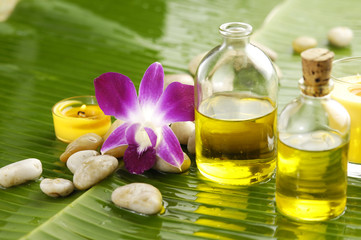 Health spa with massage oil and pink orchid on leaf