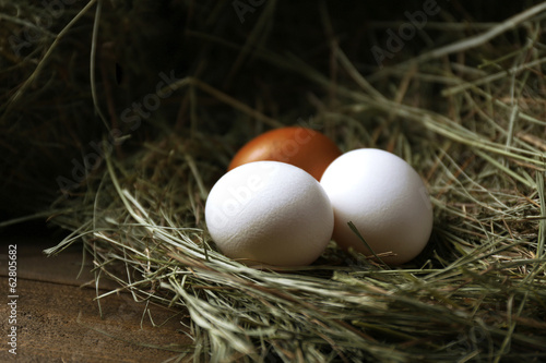Eggs on hay, on brown background