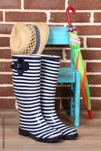 Composition with pair of colorful gumboots, chair, hat,