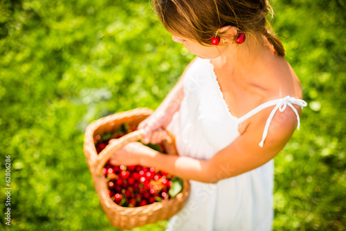 Beautiful young woman holding a basket filled with freshly picke