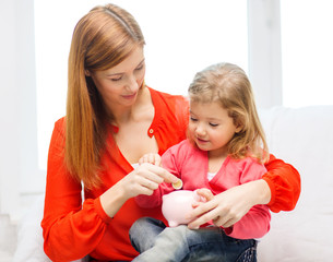 happy mother and daughter with small piggy bank