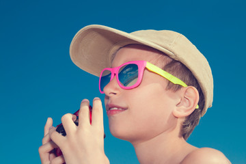 Beatiful child wearing sunglasses holding a camera on beach