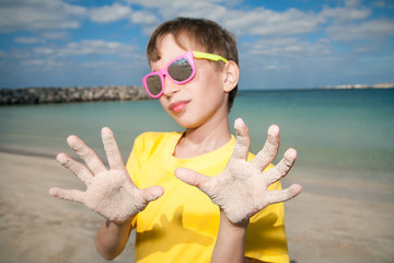 Cute child with sunglasses stands on beach showing hands