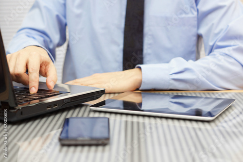 businessman in suit on office typing on laptop and watching  tab