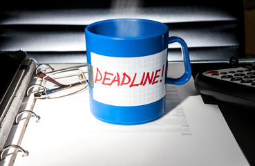 """A coffe cup with message """"deadline"""" on an office table"""
