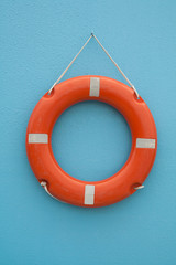 Red life buoy hanging on a blue wall. Help and support concept.