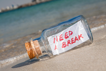 "Vacation and stress concept. Bottle with message ""need a break"""