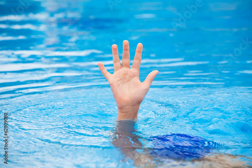 Hand of a drowning person stretching out of water