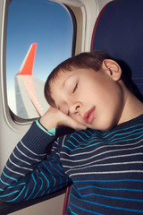 Beautiful child travelling by airplane sleeping by window