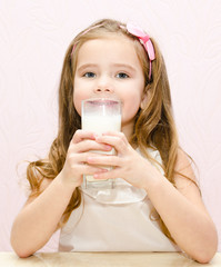 Beautiful smiling little girl drinking milk
