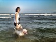 Asian woman and bull terrier on ter beach