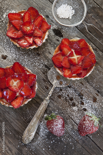 strawberries cakes with cream and icing sugar on rustic table
