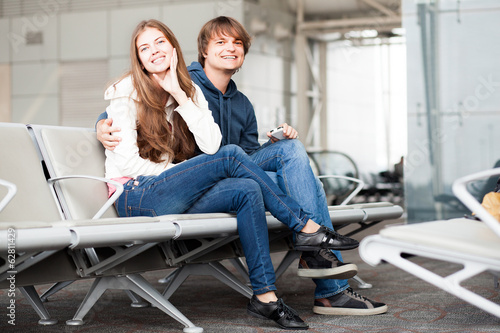 happy couple waiting for their flight in airport terminal at