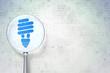 Finance concept: Energy Saving Lamp with optical glass on