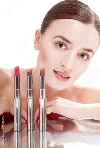 Young beautiful woman near the glamour red lipsticks,  isolated