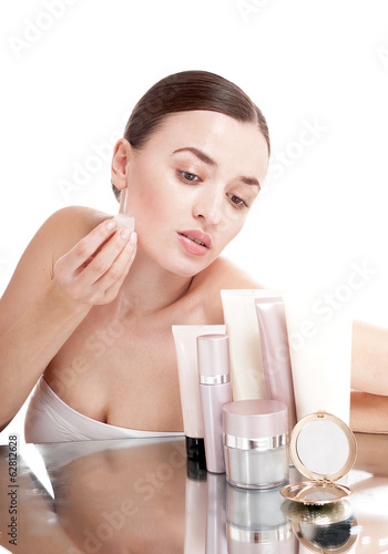 Woman applying  ice cube treatment on face - isolated on white b