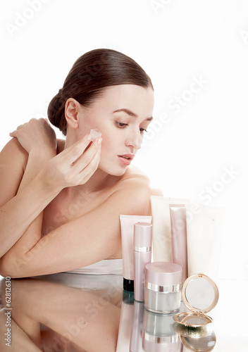 Beautiful woman applying  ice cube treatment on face. Skin care