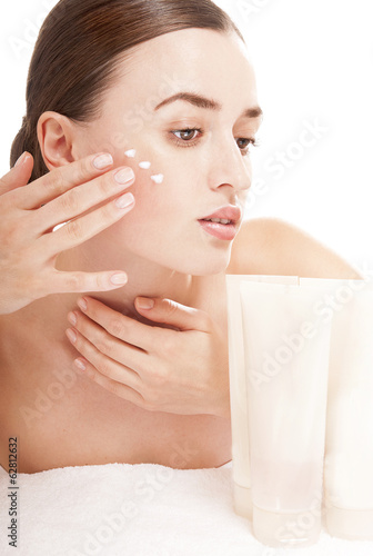 Sensual woman applying cosmetic cream treatment on her face. Ski