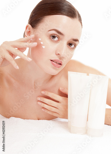 Woman applying moisturizer cream on face. Skin care consept.