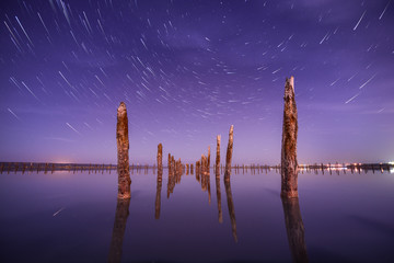 Poles in the water at night on a background star trails