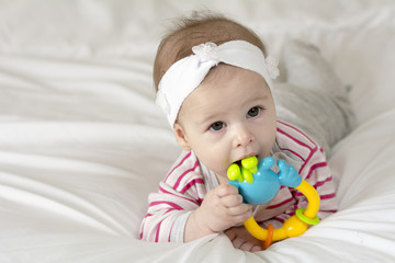 Portrait of a cute baby girl, playing with a teething toy.