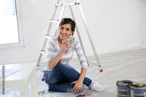 Brunette girl having a break while renovating home