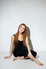 Skinny girl with long legs in black dress sitting on a white flo