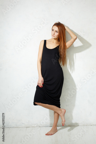 Skinny girl with long legs in black dress standing on a white fl