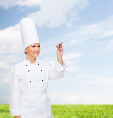 smiling female chef writing something on air