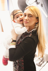 Closeup portrait of aged blonde woman holding baby girl on hands