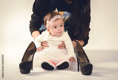 Baby with mother and looking at high heel shoes