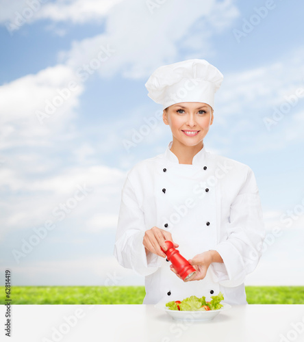 smiling female chef with preparing salad