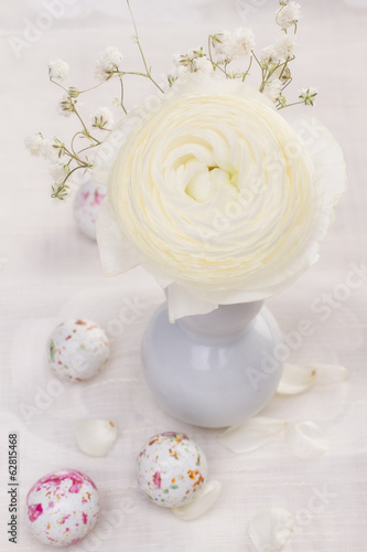 White ranunculus flower and chocolate easter candy