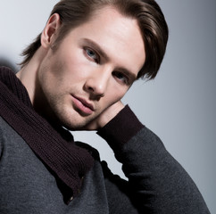 Portrait of sexy young man with hand near face.
