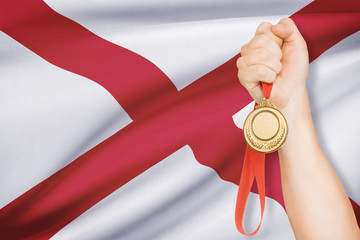 Medal in hand with flag on background - State of Alabama.