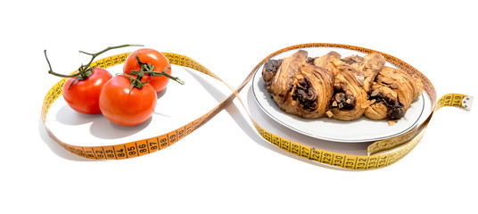 Cake on a plate and tomatoes on a branch in a centimeter tape