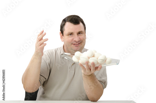 Happy seller holding a glass basket of white chicken eggs