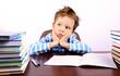 Pensive little boy sitting at a desk