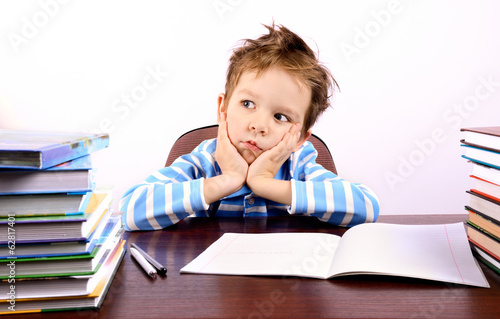 Pensive little boy sitting at a desk