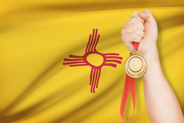 Medal in hand with flag on background - State of New Mexico.