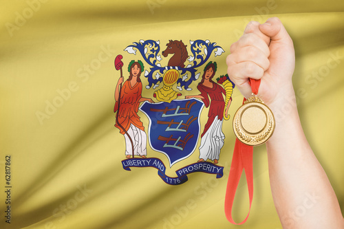 Medal in hand with flag on background - State of New Jersey.