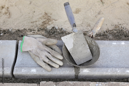 Mason equipment, trowel, protective gloves at curbstone