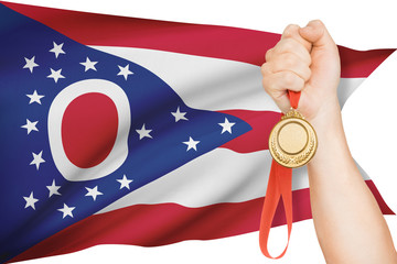 Medal in hand with flag on background - State of Ohio.